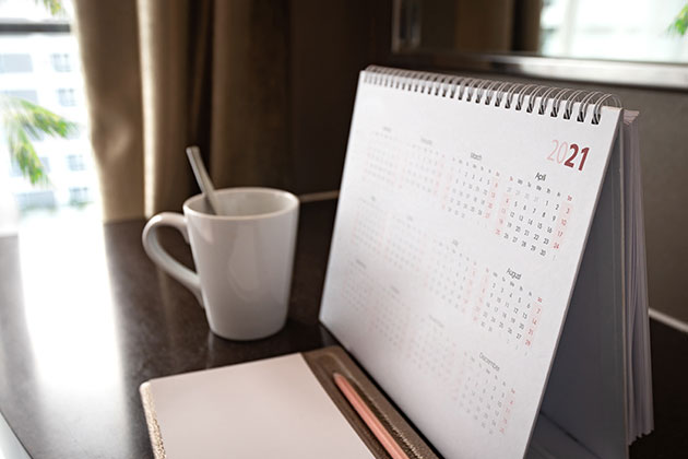 caneca de café na mesa e calendário simulando como produzir no escritório de advocacia